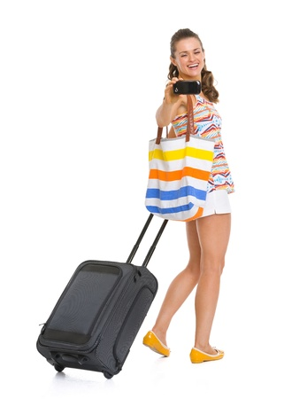 Happy young tourist woman with wheel bag taking photos with cell phone photo