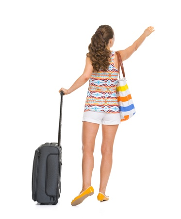 catching taxi: Full length portrait of tourist woman with wheel bag catching taxi . rear view