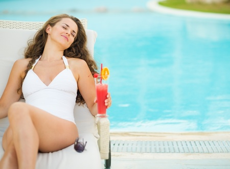 Happy young woman with cocktail enjoying laying on chaise-longue Stock Photo - 19406663