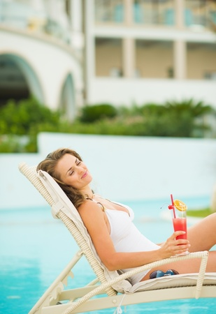 Happy young woman with cocktail enjoying laying on chaise-longue Stock Photo - 19406640