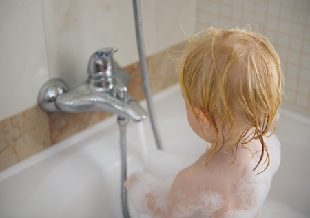 foamy: Baby washing in foamy bathtub Stock Photo