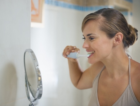 Happy young woman brushing teeth photo