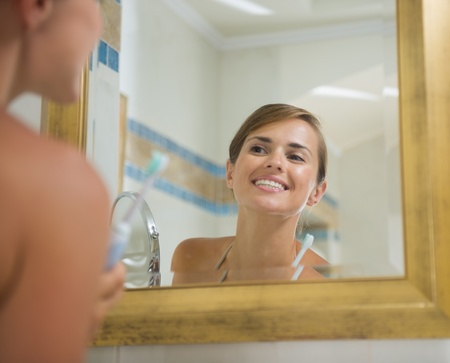 Happy young woman checking teeth after brush photo