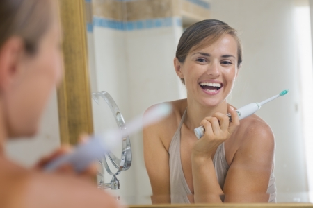 Happy young woman enjoying clean teeth after brushing electric teeth brush photo