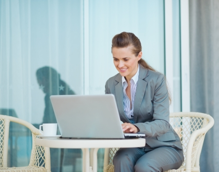 Happy business woman working with laptop on terrace photo