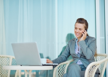 Happy business woman talking mobile phone on terrace photo