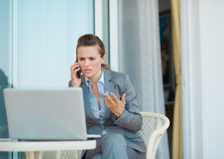 disquieted: Concerned business woman talking cell phone on terrace