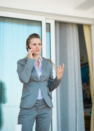 disquieted: Business woman talking mobile phone on terrace Stock Photo