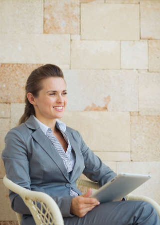 topicality: Happy business woman with tablet pc sitting on terrace