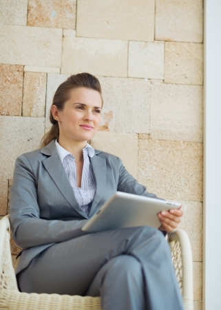 Thoughtful business woman with tablet pc sitting on terrace Stock Photo - 19406622