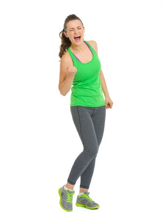 Full length portrait of happy fitness young woman rejoicing success photo