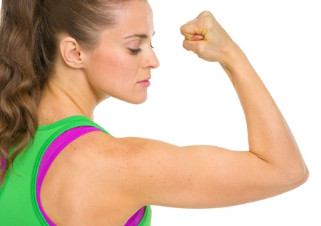 Fitness young woman showing biceps photo