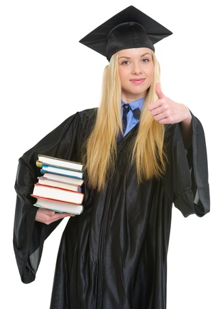 Happy young woman in graduation gown showing books and thumbs up Stock Photo - 19614360