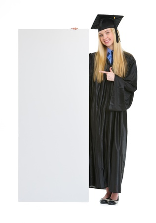 Happy young woman in graduation gown pointing on blank billboard Stock Photo - 19614278