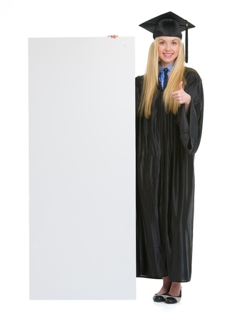 Happy young woman in graduation gown showing blank billboard and thumbs up photo