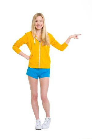 Full length portrait of happy teenager girl pointing on copy space Stock Photo - 19614204