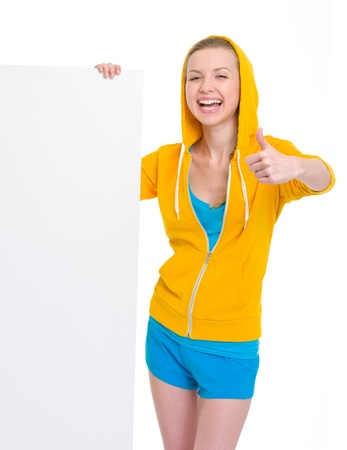 Smiling teenager girl showing blank billboard and thumbs up photo
