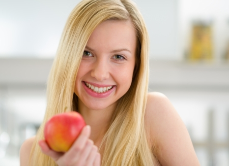 Portrait of smiling teenager girl with apple in kitchen photo
