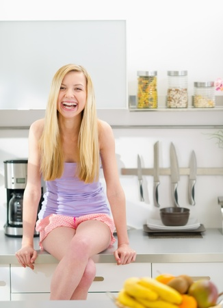 Portrait of smiling teenager girl sitting in modern kitchen photo