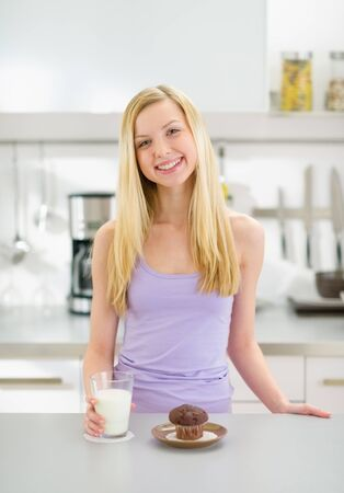 Happy teenager girl with glass of milk and chocolate muffin in kitchen photo
