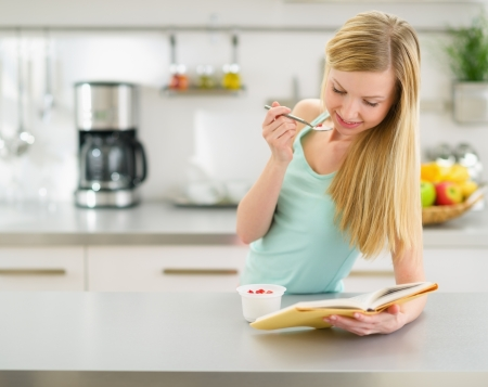 youthfulness: Happy teenager girl reading book and eating yogurt in kitchen