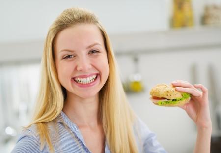 Feliz chica adolescente comiendo sándwich en la cocina Foto de archivo - 19727937