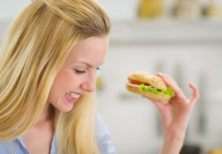 Happy young woman eating sandwich in kitchen photo