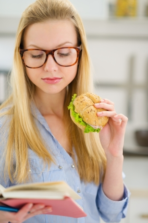classbook: Young woman eating sandwich and reading book