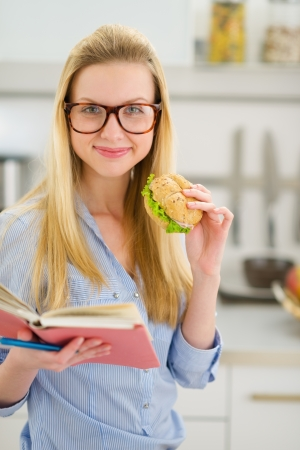classbook: Happy teenager girl eating sandwich and reading book Stock Photo