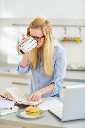 Young woman drinking coffee while studying in kitchen photo