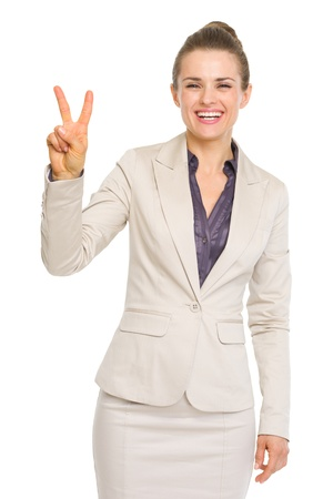 Smiling business woman showing victory gesture photo