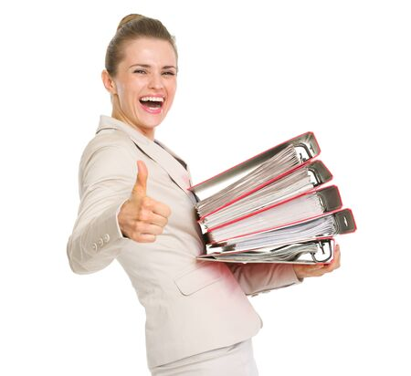 Smiling business woman holding stack of folders and showing thumbs up photo
