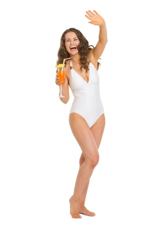 Full length portrait of smiling young woman in swimsuit with cocktail saluting photo