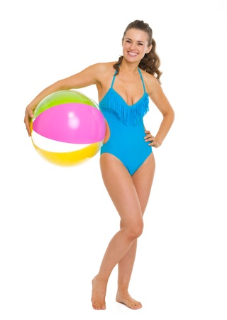 Full length portrait of happy young woman in swimsuit with beach ball photo