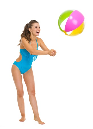 Full length portrait of smiling young woman in swimsuit playing with beach ball photo