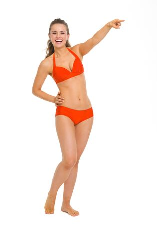Full length portrait of smiling young woman in swimsuit pointing on copy space Stock Photo - 19727599