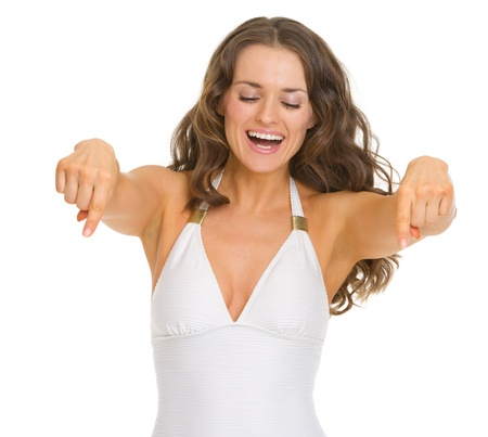 Smiling young woman in swimsuit pointing down on copy space photo