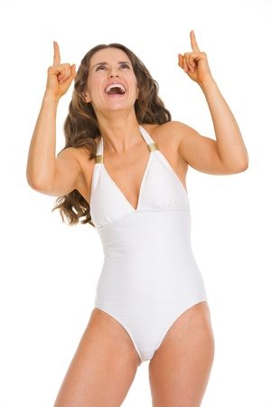 Smiling young woman in swimsuit pointing up on copy space photo