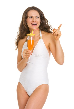 Smiling young woman in swimsuit with cocktail pointing on copy space photo