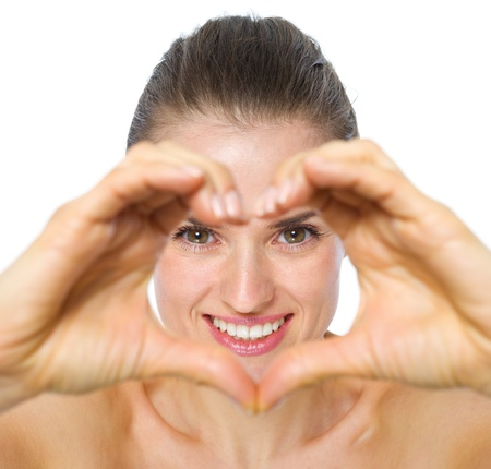 Smiling young woman looking through heart shaped hands photo