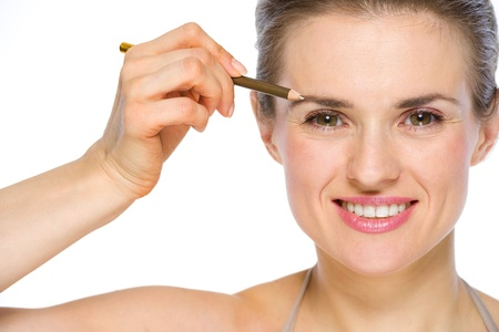 Beauty portrait of happy young woman applying brown eye liner Stock Photo - 19848830