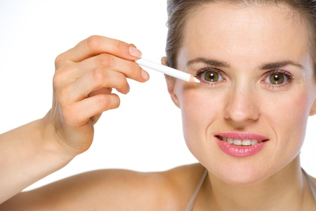 Beauty portrait of young woman applying white eye liner Stock Photo - 19848834