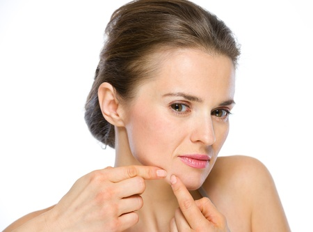 Beauty portrait of young woman squeezing acne photo