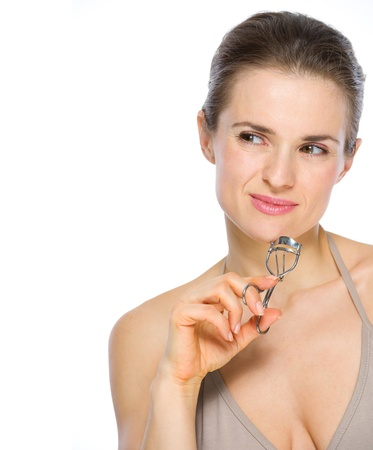Beauty portrait of young woman holding eyelash curler and looking on copy space Stock Photo - 19848799