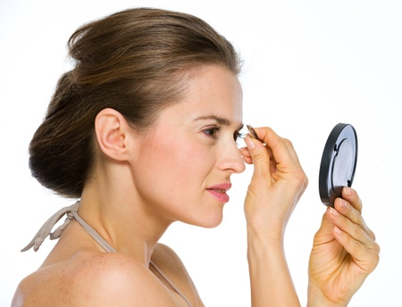 Beauty portrait of young woman looking into mirror and using tweezers Stock Photo - 19848828