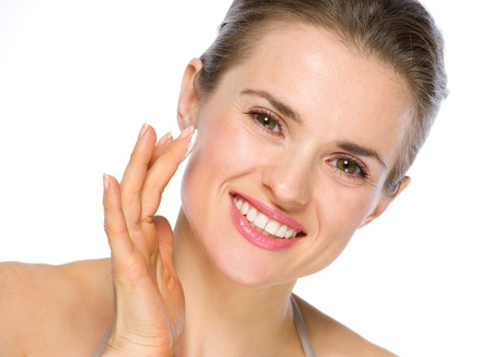 Beauty portrait of smiling young woman applying creme photo