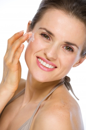 Beauty portrait of happy young woman applying creme photo