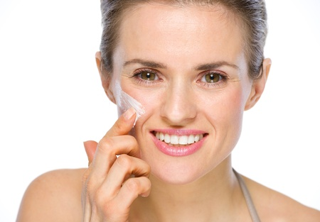 Beauty portrait of happy young woman applying creme on cheek photo