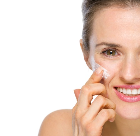 Closeup on happy young woman applying creme on cheek photo
