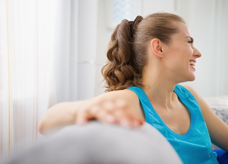 Smiling young woman sitting on divan in living room Stock Photo